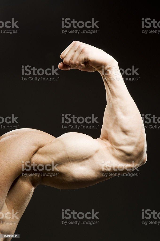 Flexed man's biceps on black background royalty-free stock photo