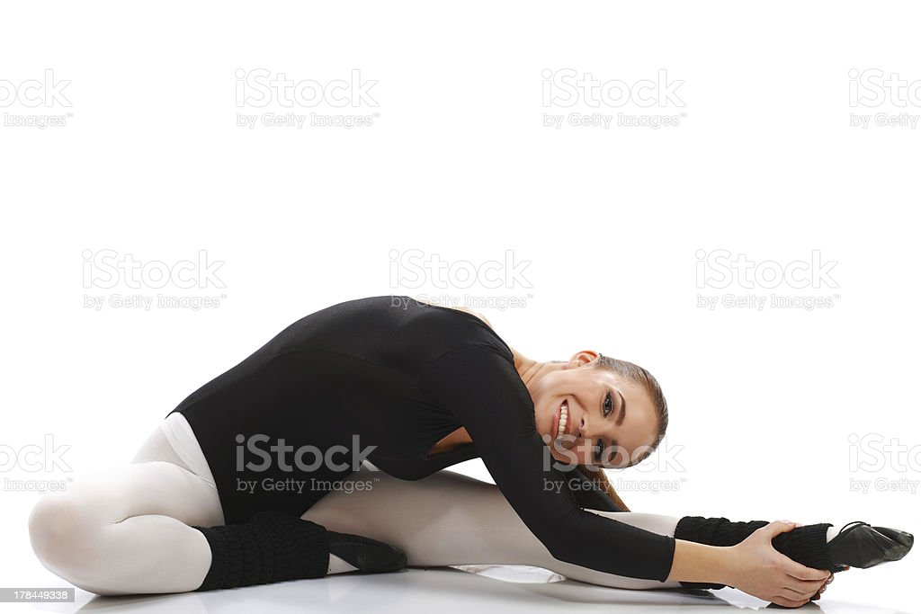 Flexible ballerina doing stretching exercise on a floor royalty-free stock photo