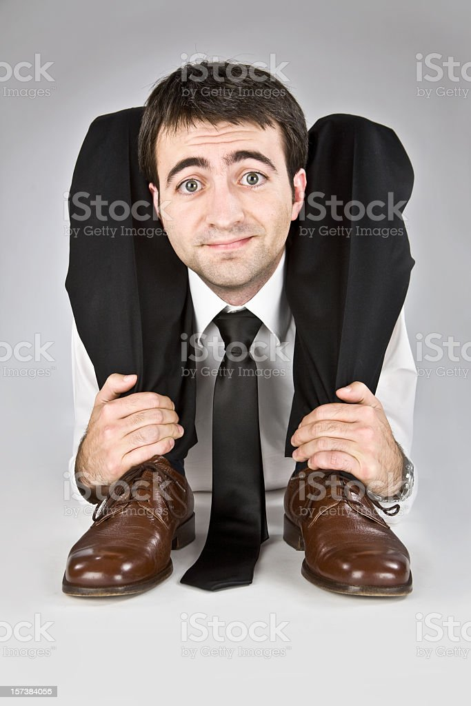 A flexible business man grabbing his ankles  stock photo