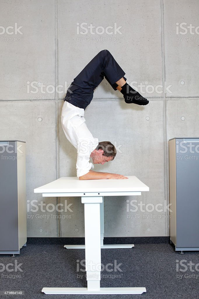 flexible business man in scorpion asana on desk in his office stock photo