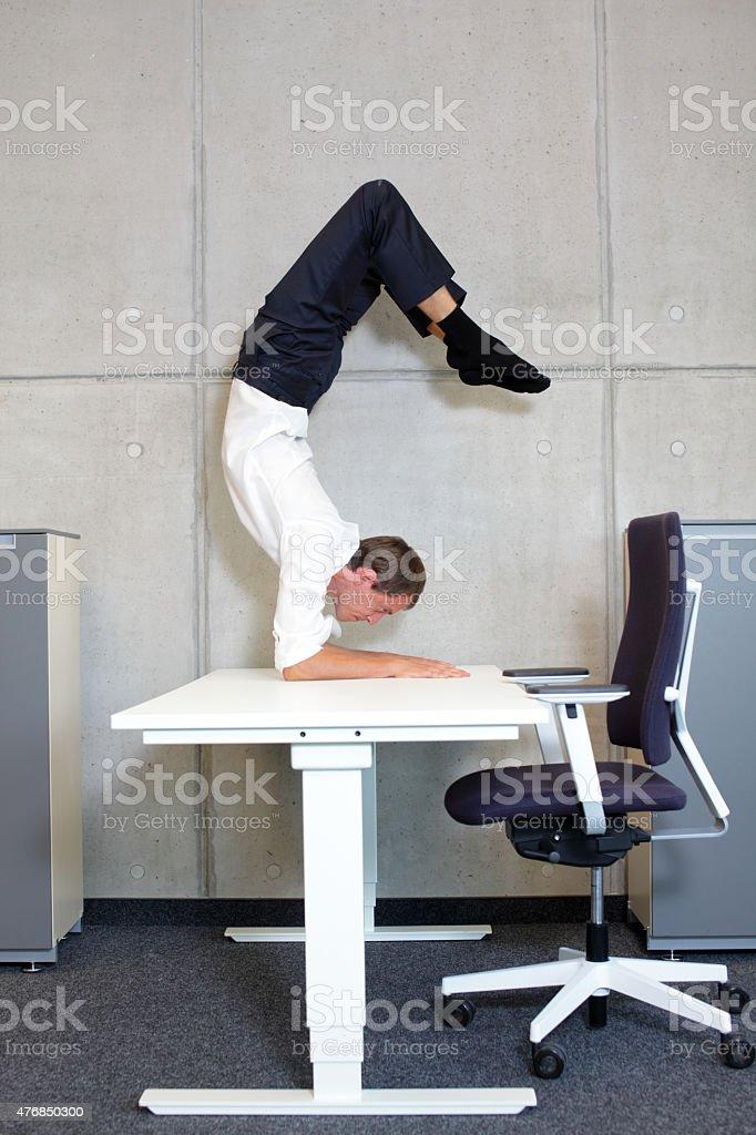 flexible business man in scorpion asana on desk stock photo