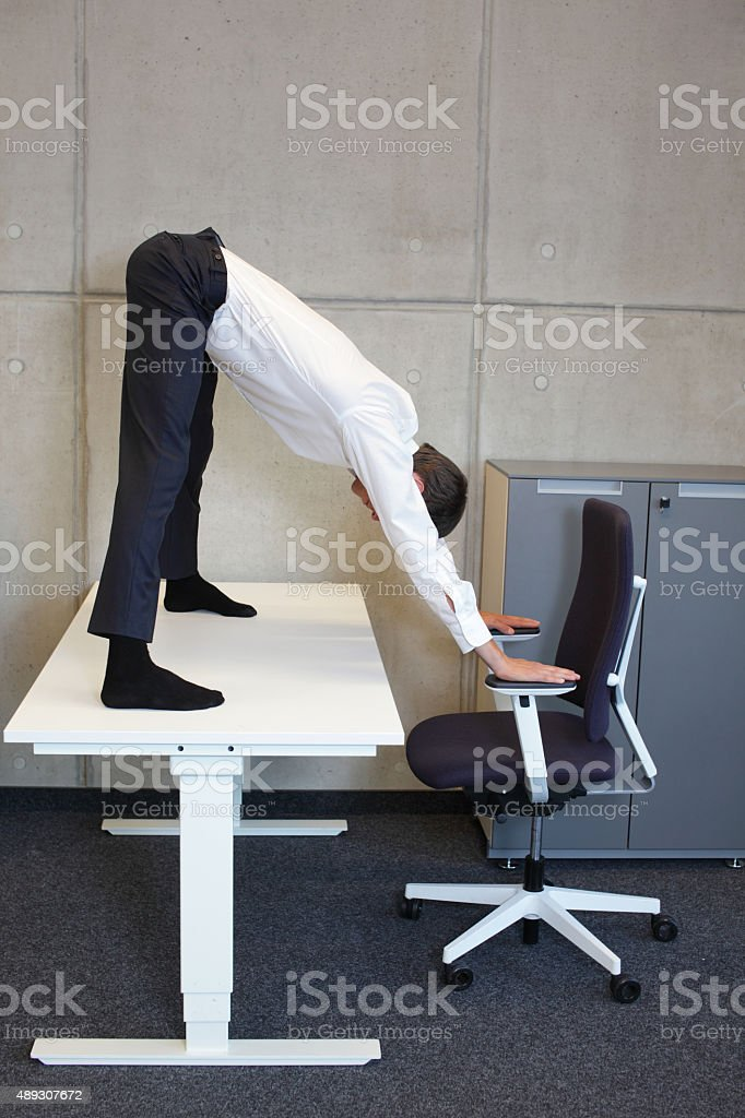 flexible business man  practicing yoga on desk in his office stock photo