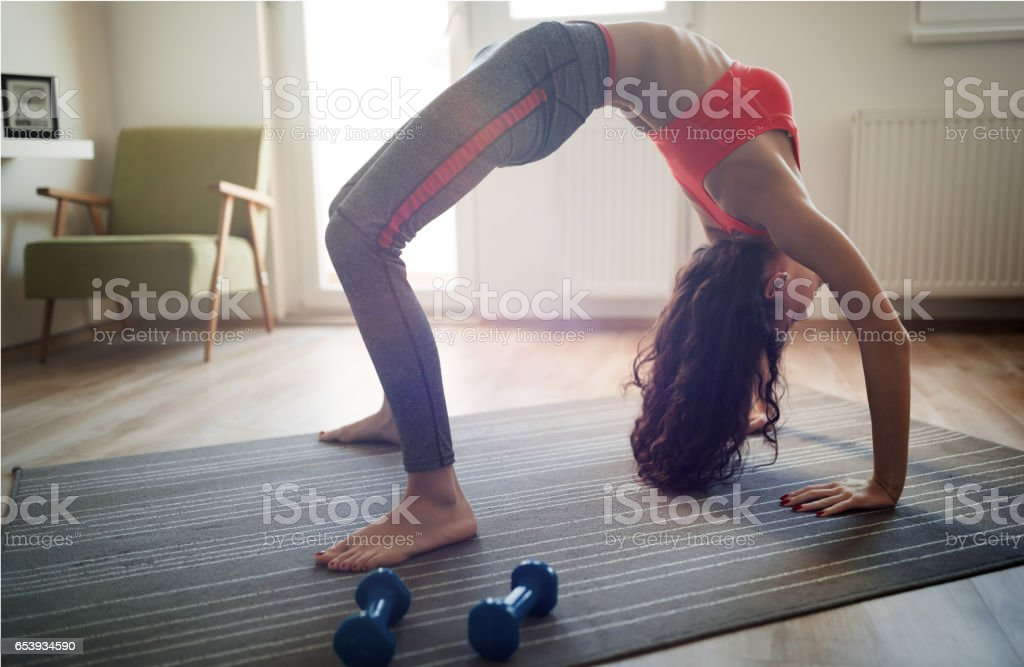 Flexible fit woman stretching at home in bridge yoga pose stock photo