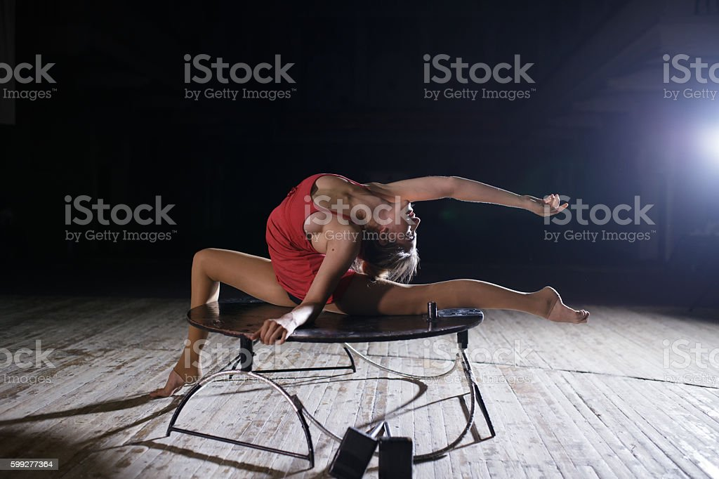 Flexible graceful woman doing artistic contortion on scene stock photo