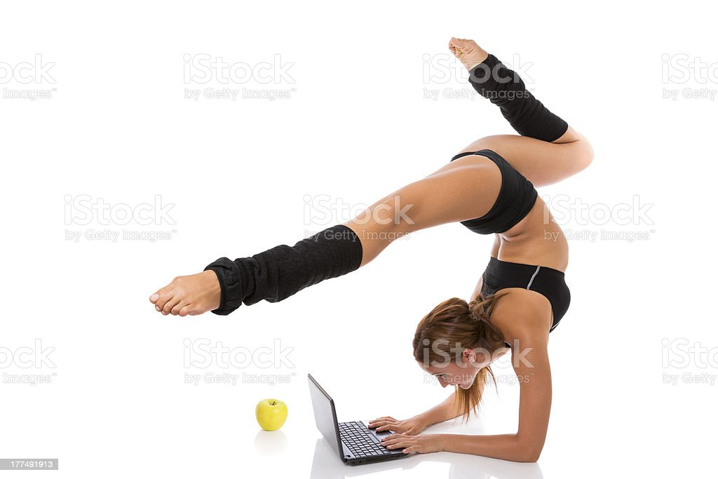 Flexible gymnast with laptop and apple royalty-free stock photo