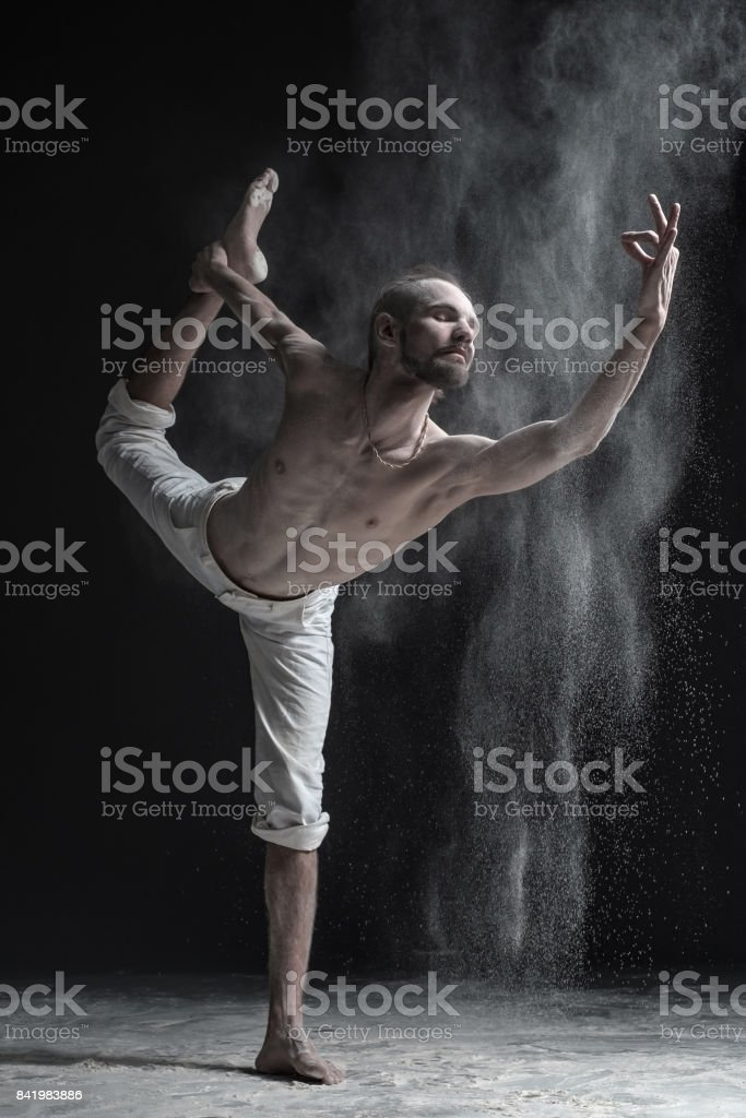 Flexible yoga man practices yoga or pilates, performing Natarajasana stock photo