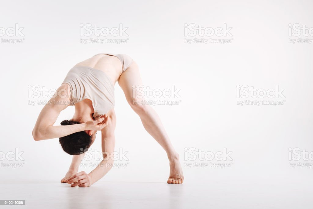 Flexile young woman demonstrating her flexibility in the studio stock photo