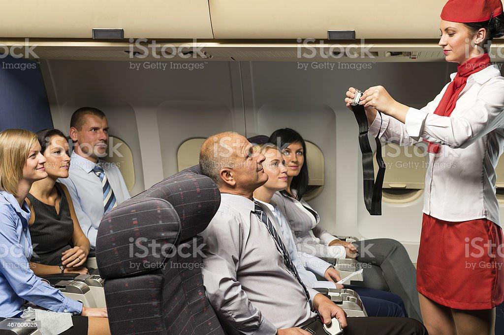 Flight attendant demo fastening seat belt airplane stock photo