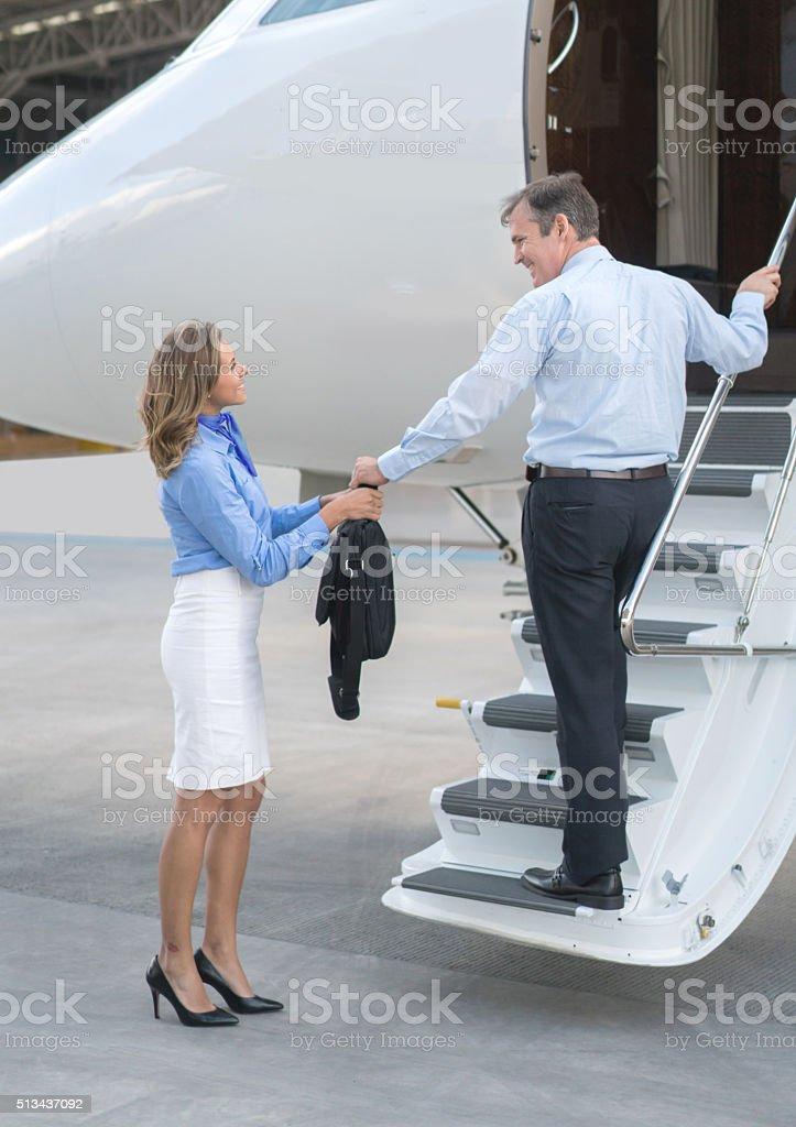 Flight attendant helping passenger traveling stock photo