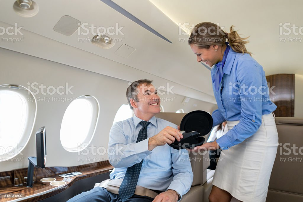 Flight attendant serving a passenger in an airplane stock photo