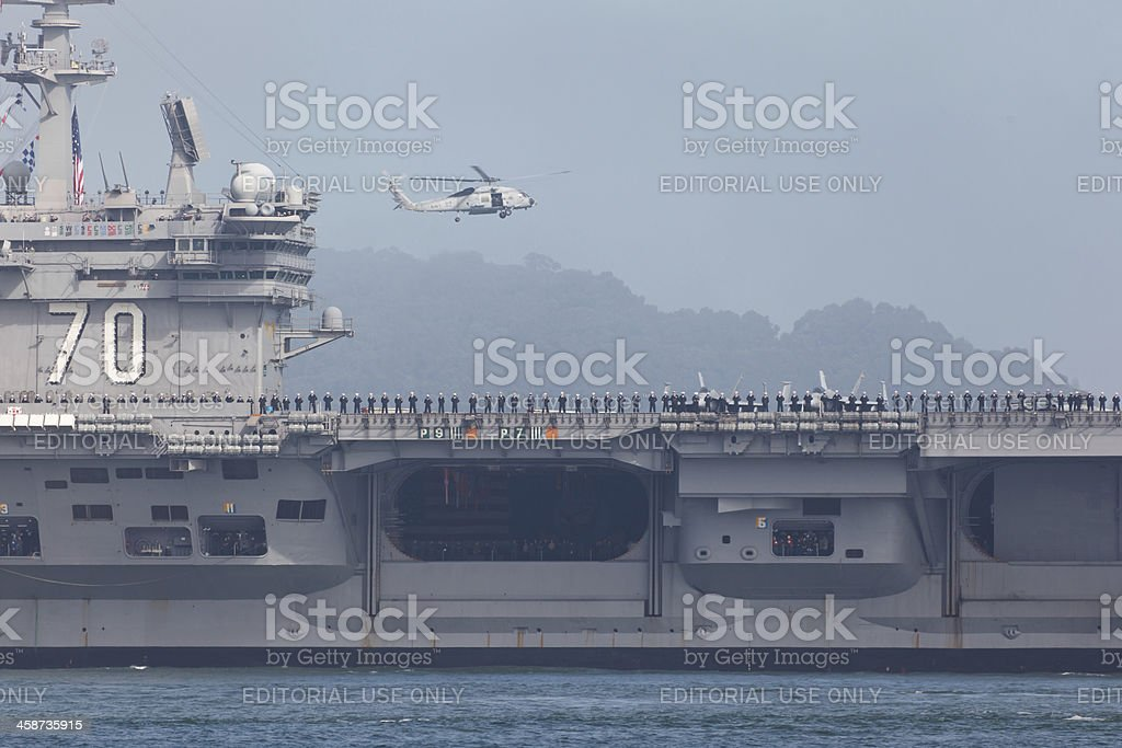 Flight deck detail of USS Carl Vinson with helicopter hovering royalty-free stock photo
