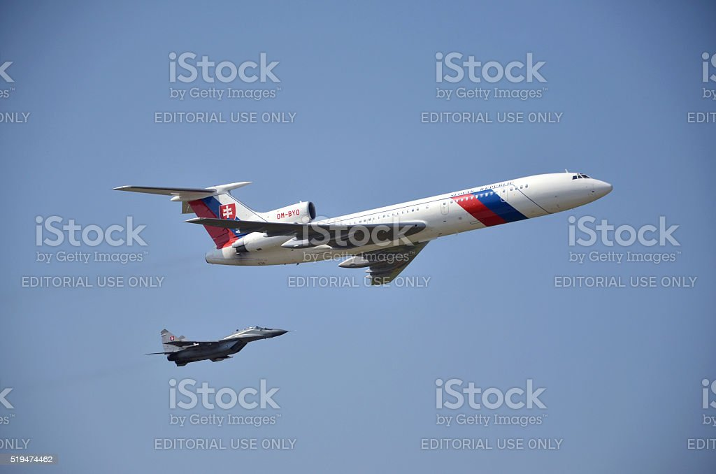 Flight display of jet airliner Tupolev Tu-154M escorted by MiG-29 stock photo