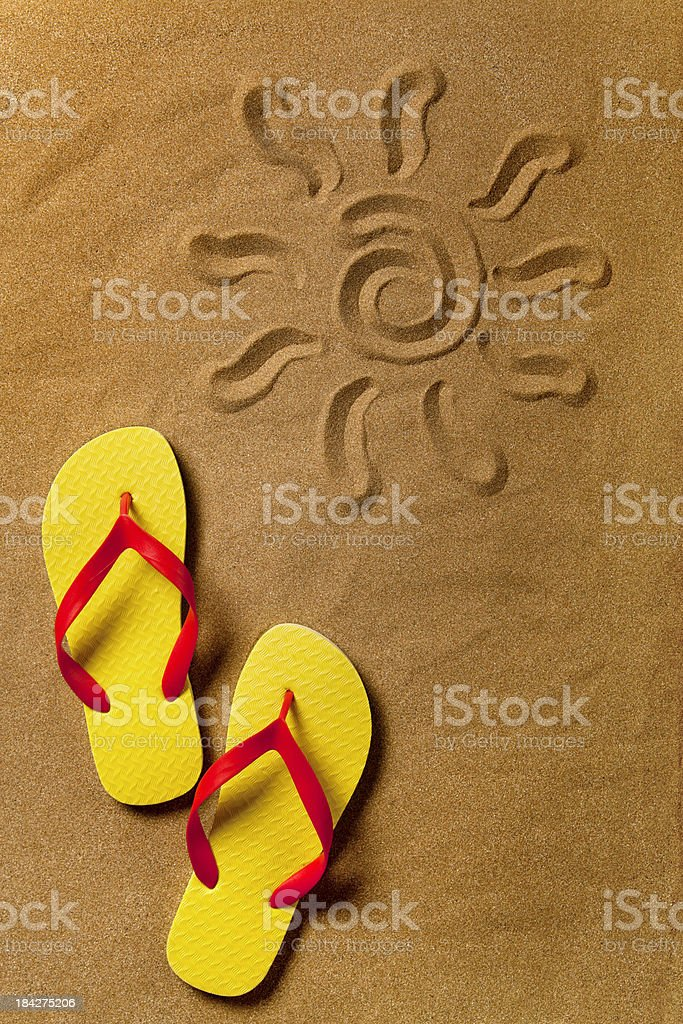 Flip flops and sun sign on the sand royalty-free stock photo