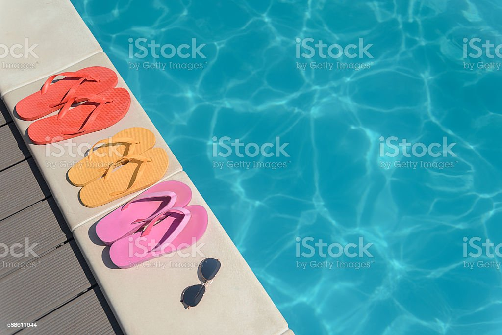 Flip flops and sunglasses near water stock photo