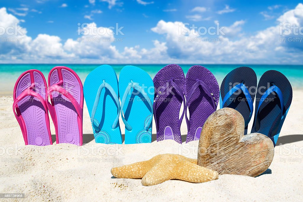 Flip flops and wooden heart on the beach stock photo