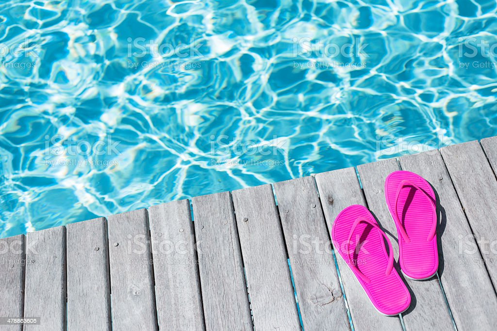 Flip flops by the swimming pool stock photo