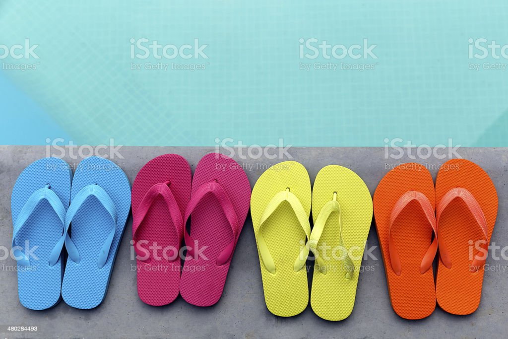 Flip flops by turquoise pool stock photo