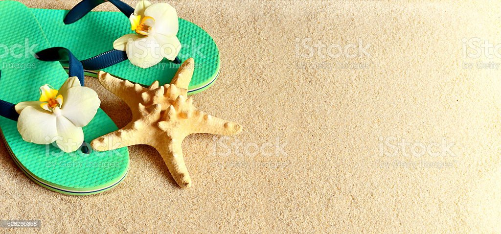 Flip Flops in the sand with starfish . Summertime .beach concept. stock photo