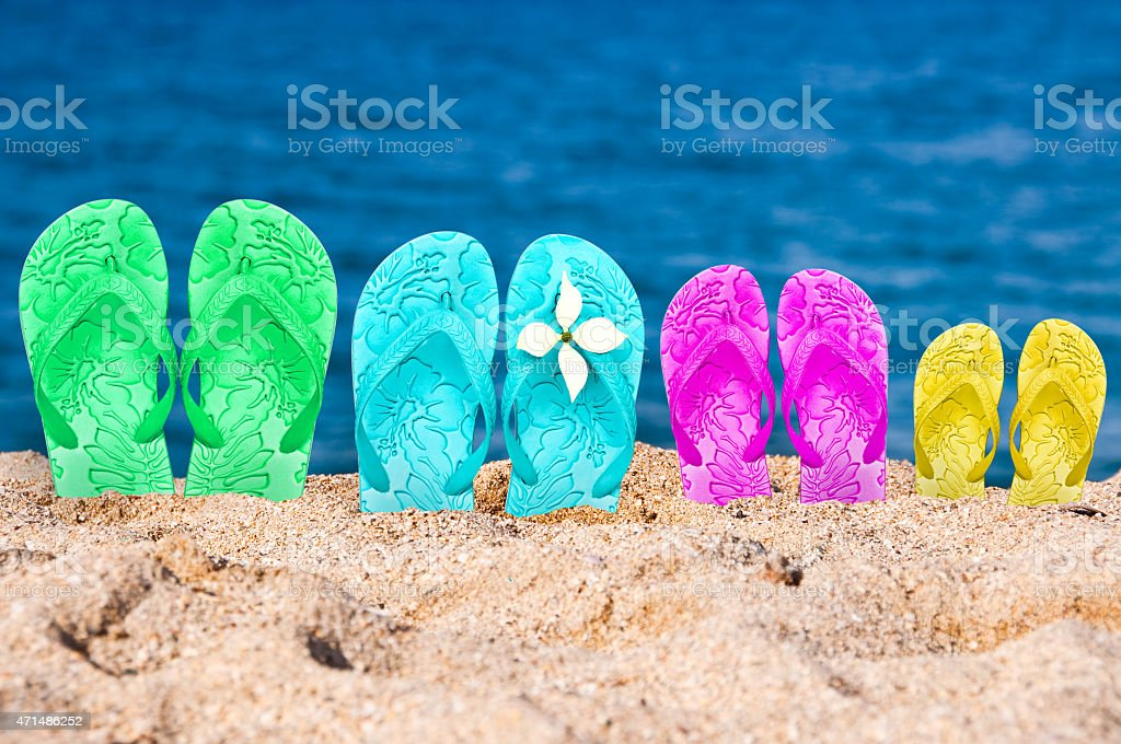 Flip flops of a family of four in the sand stock photo