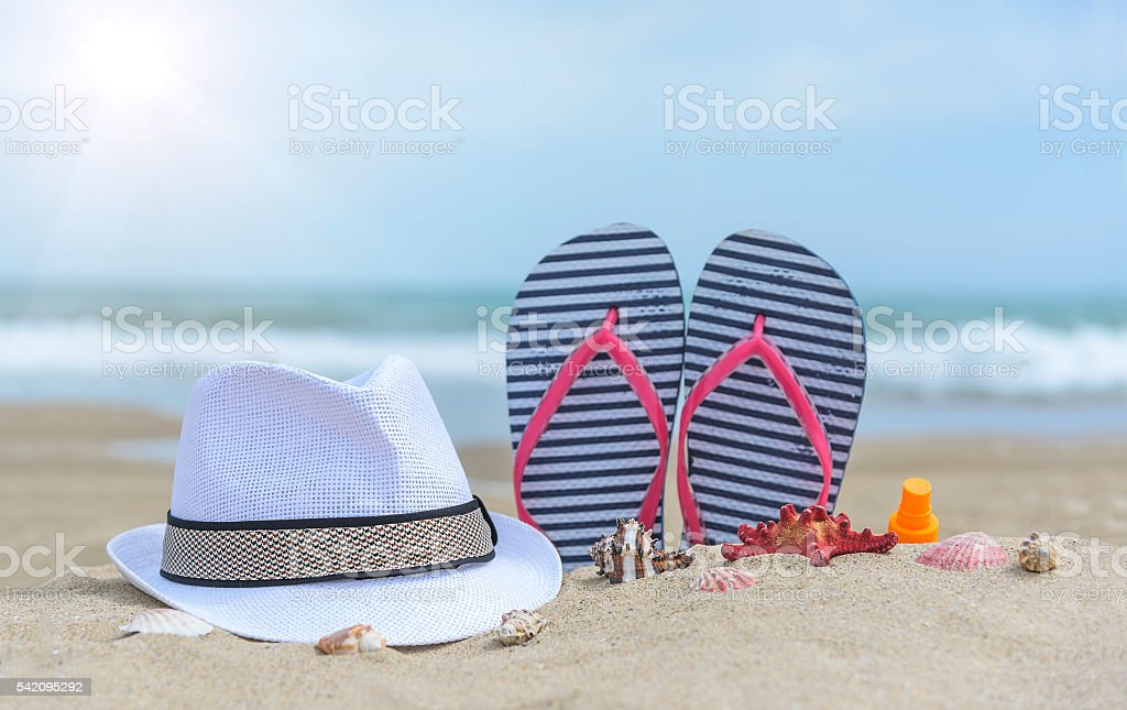 Flip-flops and shells on the beach. stock photo