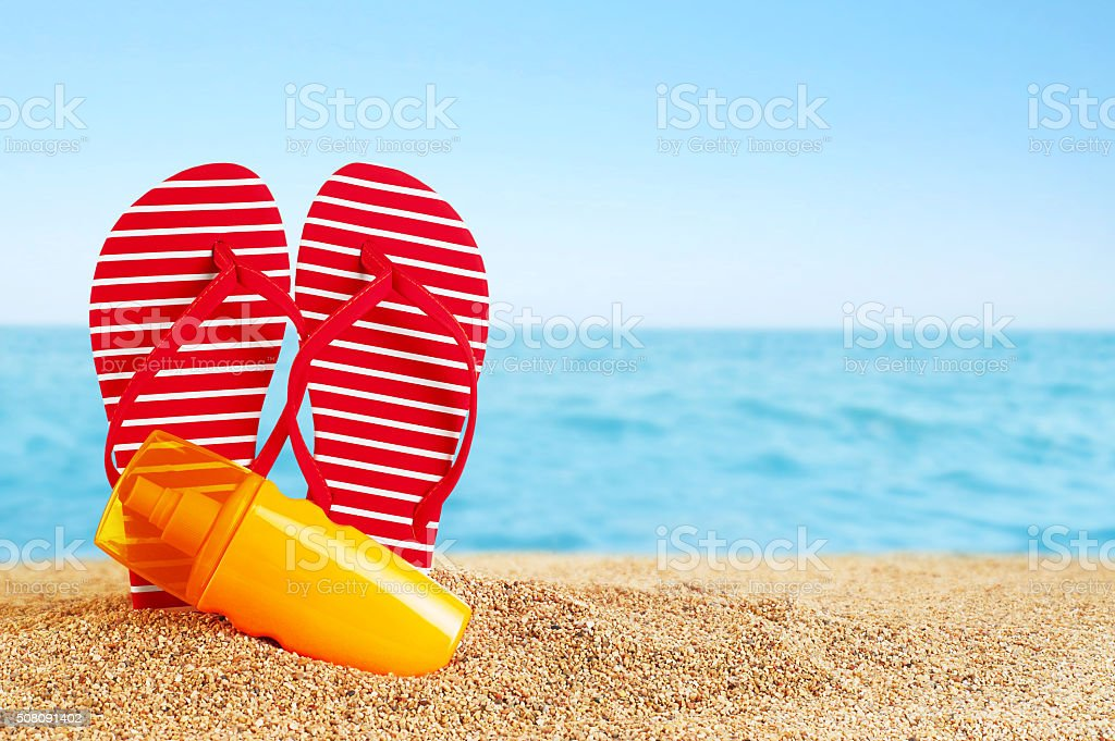 Flip-flops and sunscreen spray on the beach. stock photo