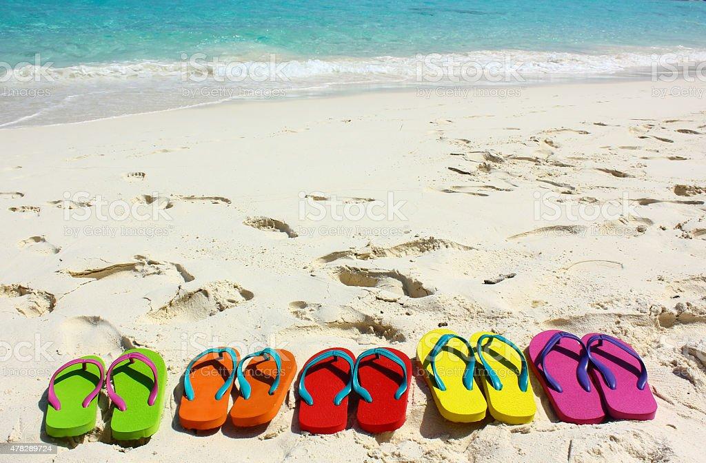 Flipflops auf einem sandigen Strand am Ozean Lizenzfreies stock-foto