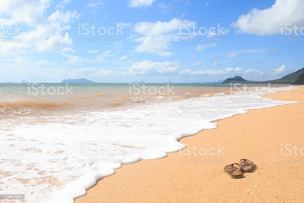 Сандалии flipflops на песчаном пляже в летнее время отдыха и отпуск. Стоковые фото Стоковая фотография