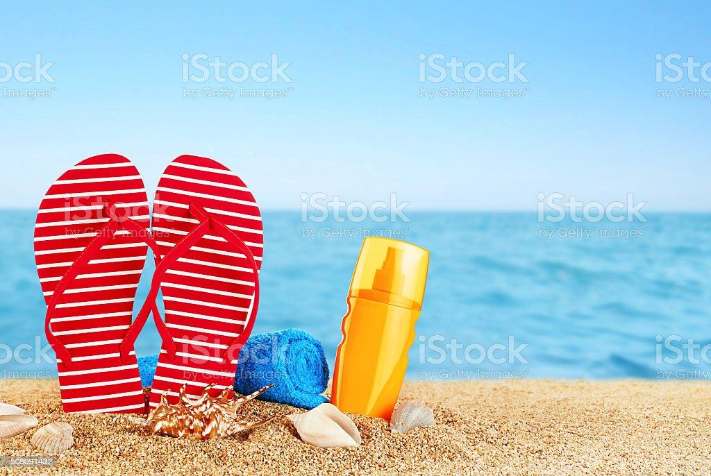 Flip-flops, sunscreen spray and towel on the beach. stock photo