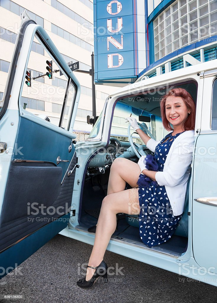 Flirtatious young woman in vintage car stock photo