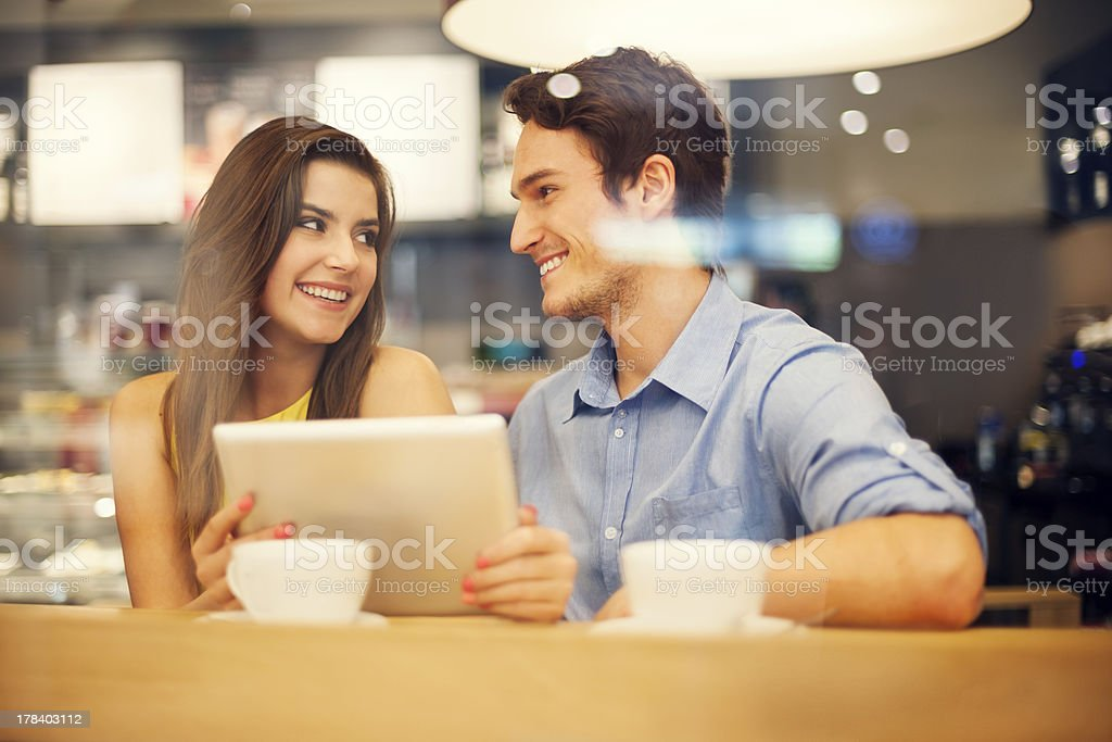 Flirting couple in cafe using digital tablet stock photo