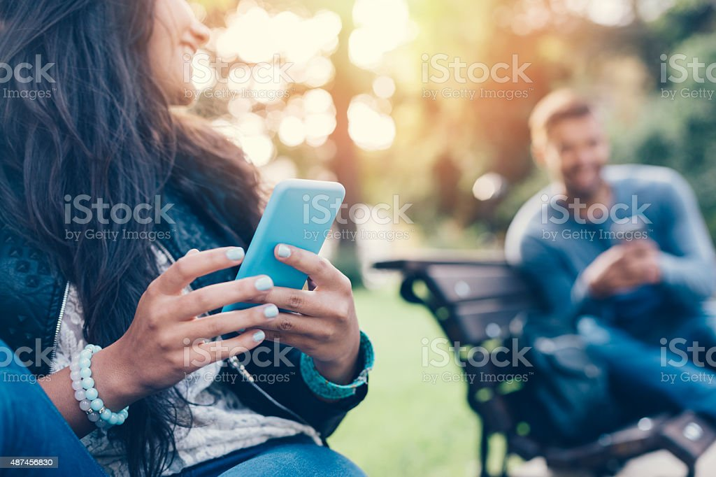 Flirting couple in the park texting on smartphones stock photo