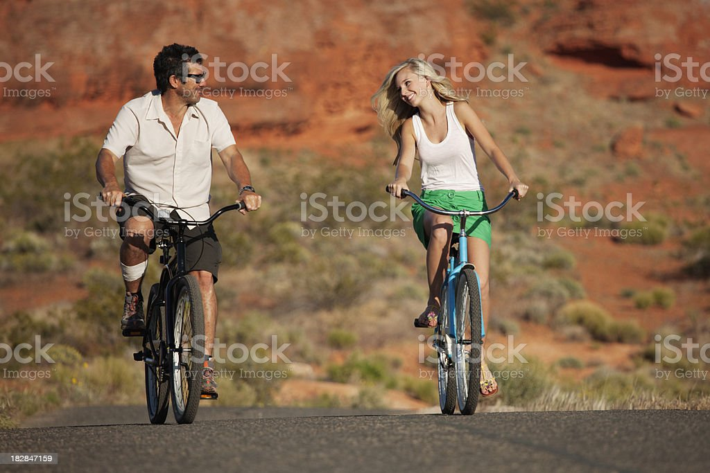 Flirting couple riding on bikes through red rock country stock photo