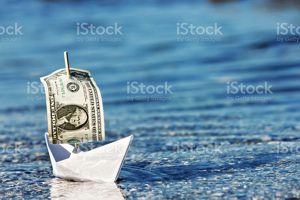 Floating a company? Paper boat with dollar bill sail stock photo