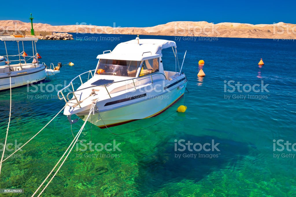 Floating boat on turquoise sea in Velebit channel, with desert island of Pag background, Karlobag, Croatia stock photo
