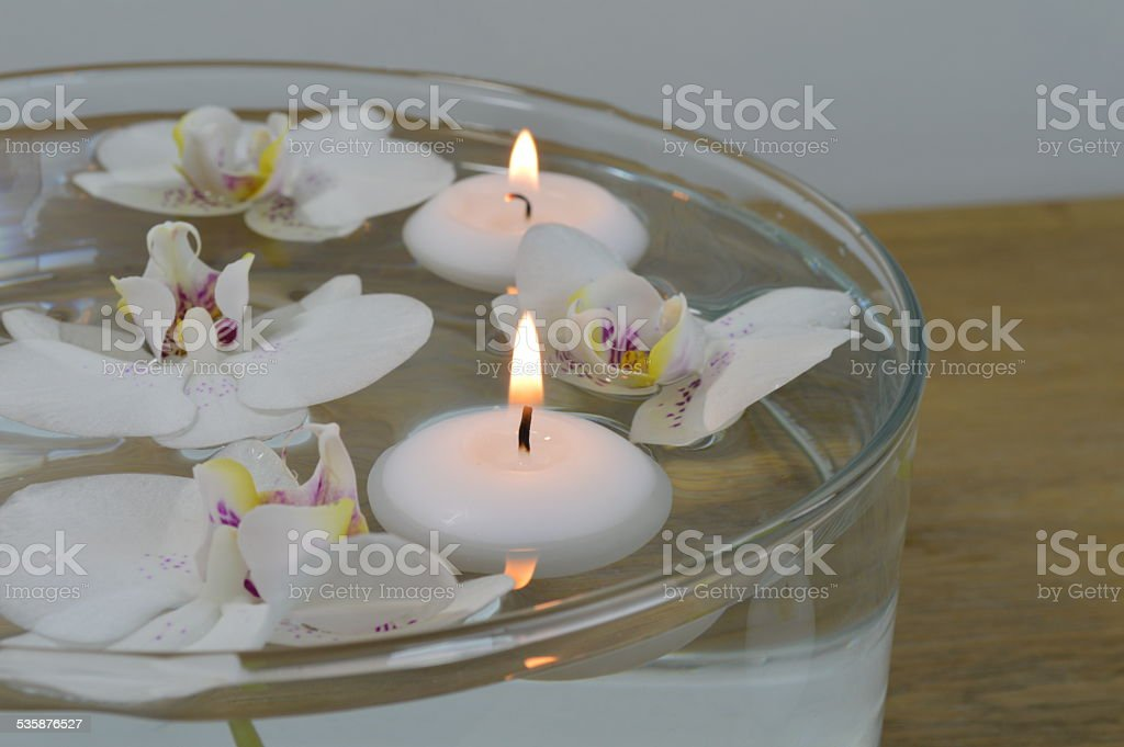 Floating candles with white and purple floating orchids stock photo