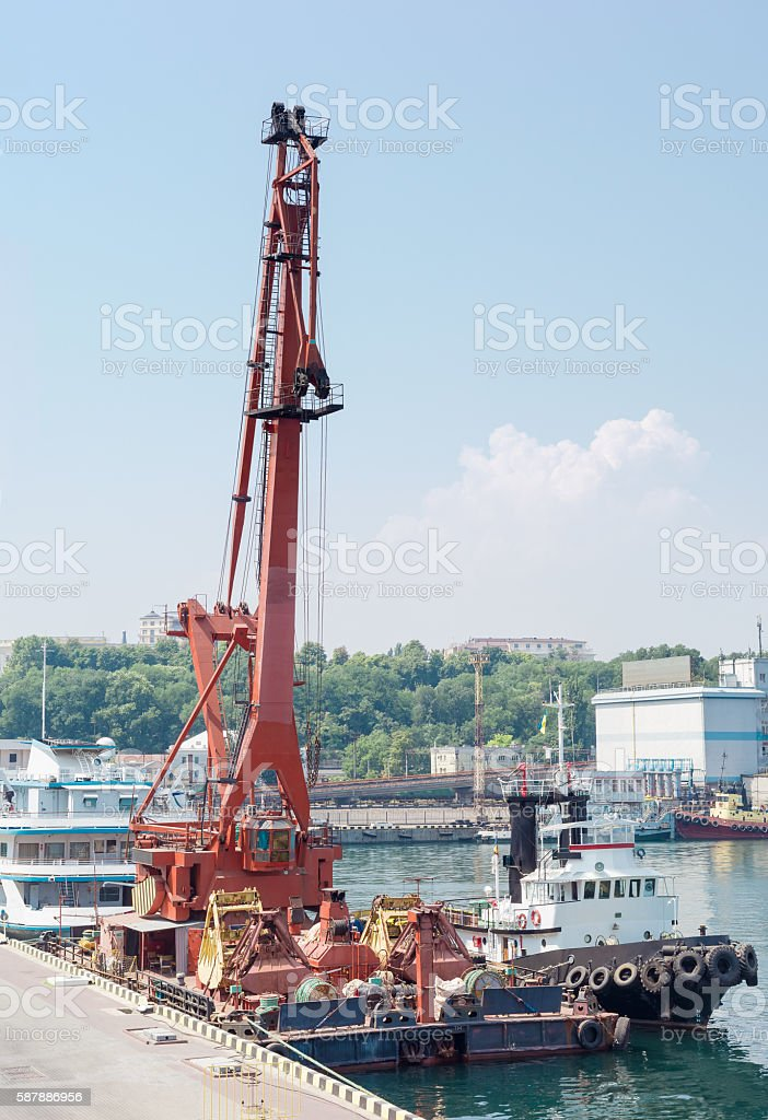 Floating crane and marine tug at the sea port berth stock photo