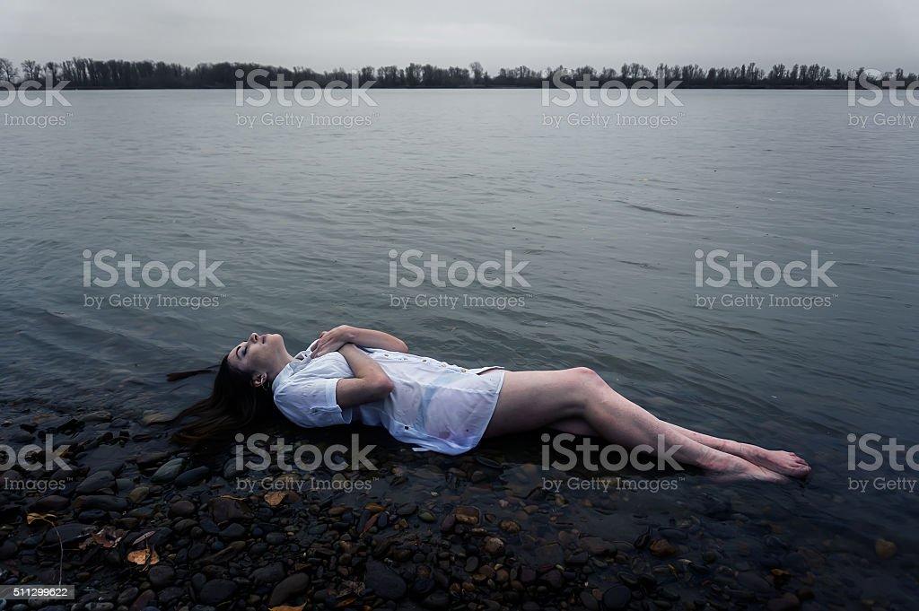 Floating girl in dark river stock photo