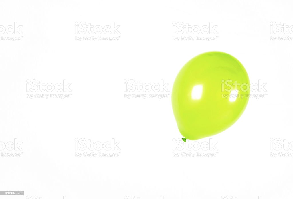 Floating green balloon in a studio royalty-free stock photo