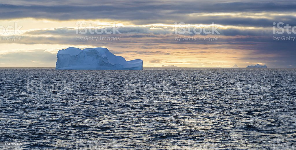 Floating Iceberg and Setting Sun in Antarctica stock photo