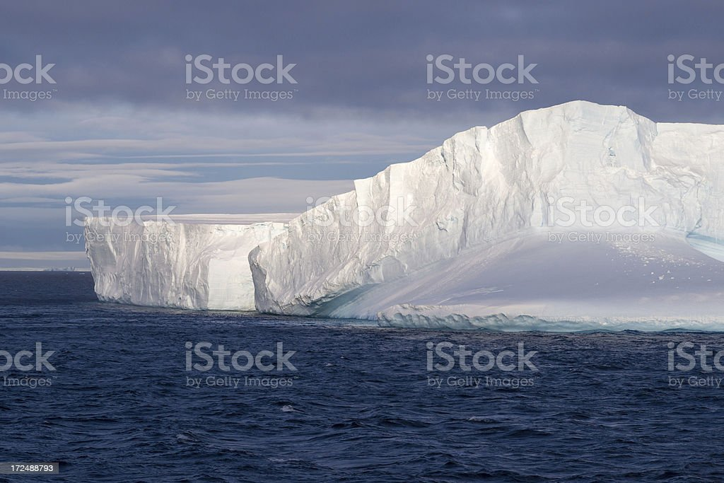 Floating Iceberg in Antarctica Lit by Setting Sun stock photo