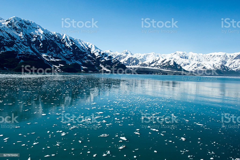 Floating iceberg pieces with mountain in the background stock photo