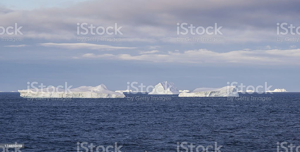 Floating Icebergs in Antarctica Lit by Setting Sun stock photo