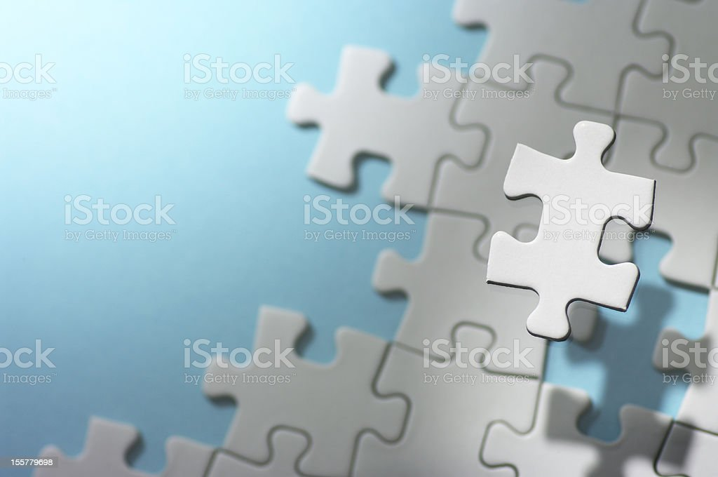 Floating jigsaw puzzle piece in spot light. stock photo