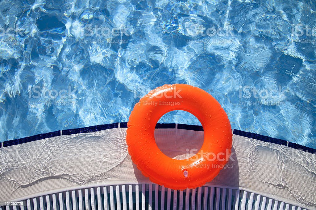 floating orange ring on edge of swimpool stock photo
