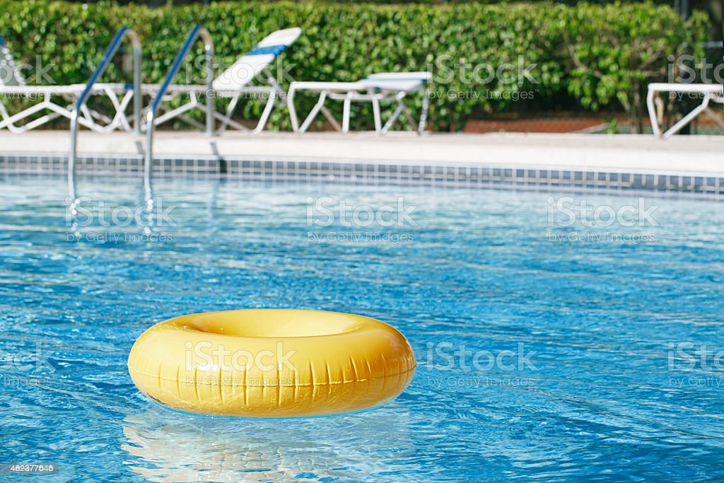floating ring on blue water swimpool with waves reflecting stock photo