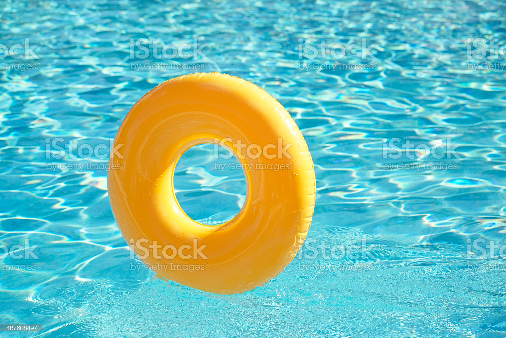 floating ring on blue water swimpool with waves reflecting royalty-free stock photo