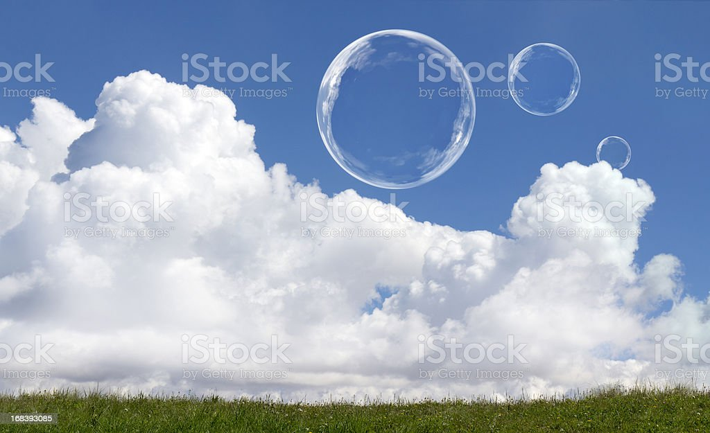 Floating Soap Bubbles Against Clear Sunlit Blue Sky and Clouds royalty-free stock photo