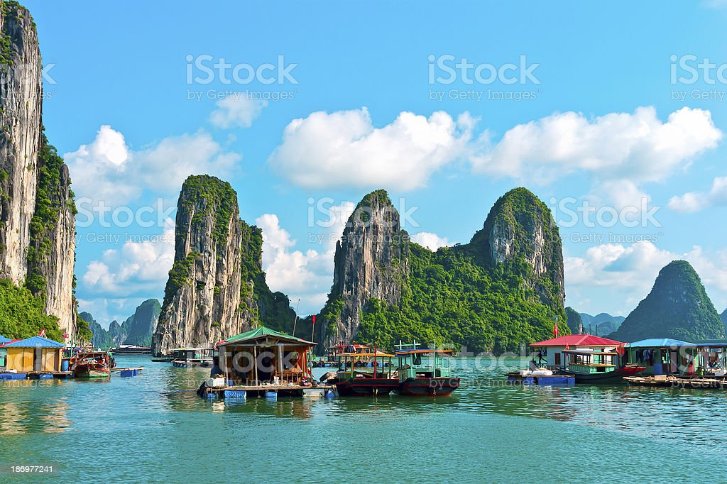 Floating village near rock islands in Halong Bay stock photo