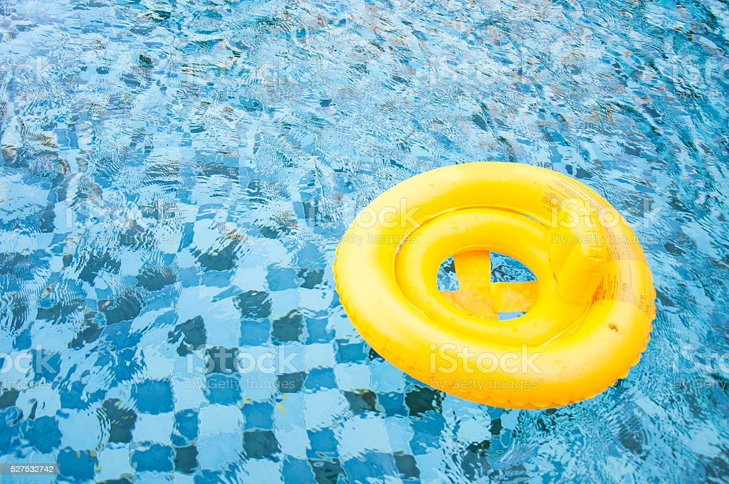 floating yellow ring on blue water swimpool with waves reflectin stock photo