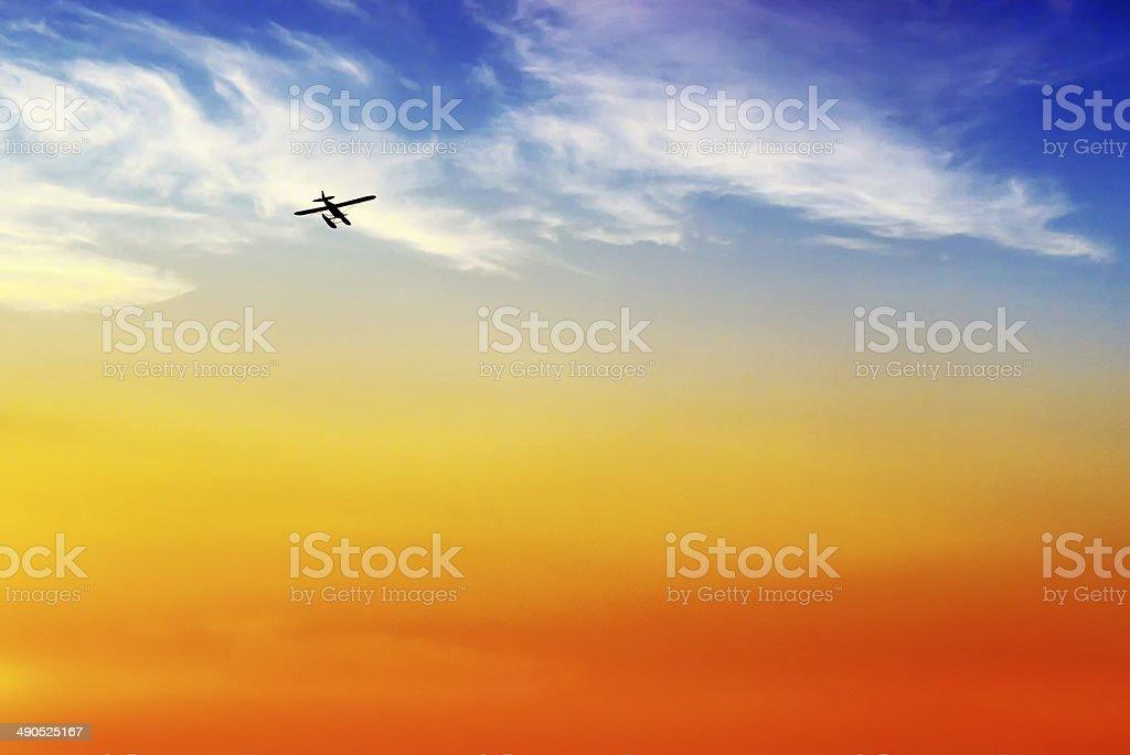 Floatplane Silhouette Flying into Sunset stock photo